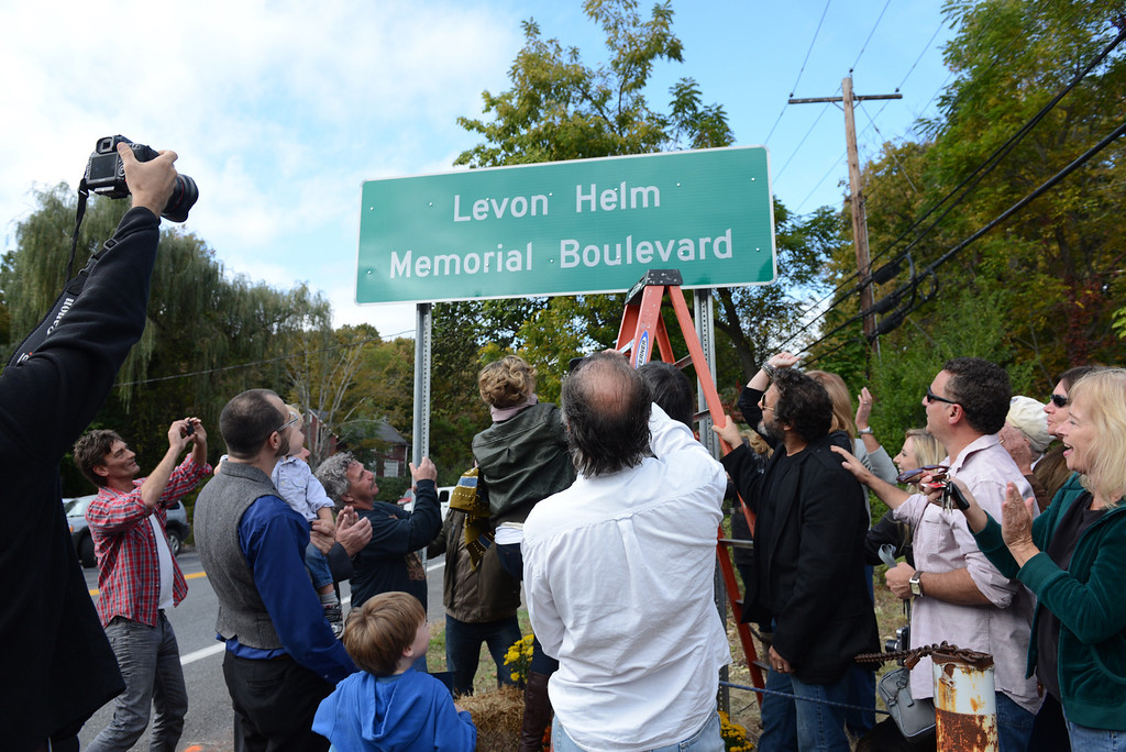 Description of . Tania Barricklo-Daily Freeman  Amy Helm, on ladder, the daughter of Levon Helm, unveils a plaque that dedicated Rt 375 in Hurley to her late father at a cermony Friday afternoon.