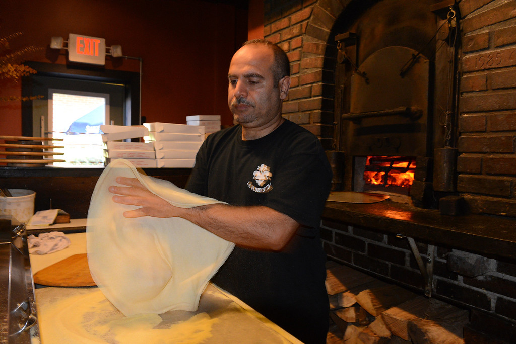 Description of . Tania Barricklo-Daily Freeman Marwan Rzek , co-owner of La Florentina, starts to throw some pizza dough in preparation of a pizza to be baked in the wood fire oven behind him..