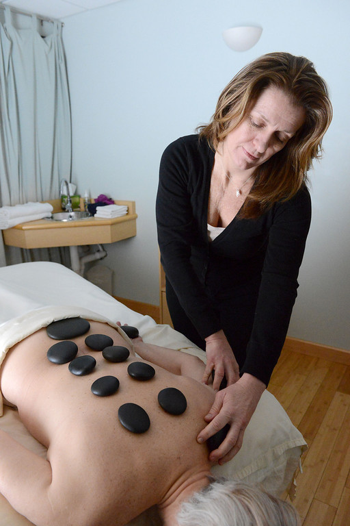 Description of . Tania Barricklo-Daily Freeman Gillian Cilibrasi, a licensed massage therapist at River Rock Health Spa in Woodstock, uses heated rocks in a treatment on Joyce Beymer Allenby.