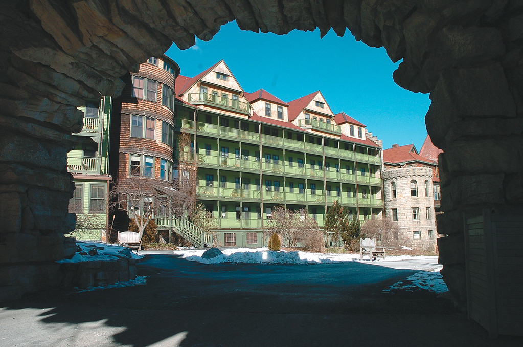 Description of . Mohonk Moutain House as seen from beneath the stone arch just off hte back porch overlooking the lake.