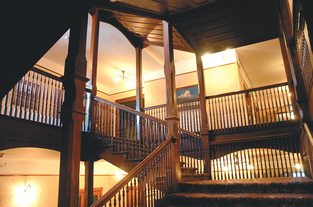Description of . A wooden staircase makes its way up all flights in the middle of the Mohonk Mountain House.