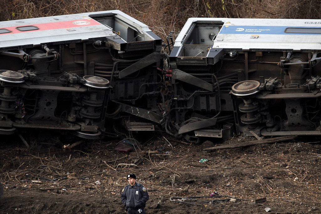 Description of . A police officer stands guard at the scene of a Metro-North passenger train derailment in the Bronx borough of New York Sunday, Dec. 1, 2013. The train derailed on a curved section of track in the Bronx on Sunday morning, coming to rest just inches from the water and causing multiple fatalities and dozens of injuries, authorities said. Metropolitan Transportation Authority police say the train derailed near the Spuyten Duyvil station. (AP Photo/John Minchillo)