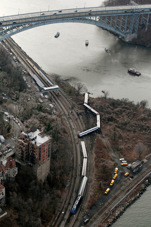Description of . A Metro-North passenger train lays on it's side after derailing in the Bronx borough of New York, Sunday, Dec. 1, 2013. The train derailed on a curved section of track in the Bronx on Sunday morning, coming to rest just inches from the water and causing multiple fatalities and dozens of injuries, authorities said. Metropolitan Transportation Authority police say the train derailed near the Spuyten Duyvil station. (AP Photo/Mark Lennihan)