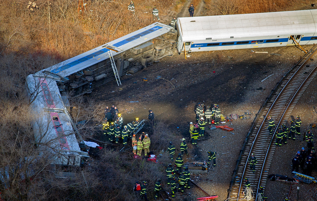 Description of . First responders work the scene of a derailment of a Metro-North passenger train in the Bronx borough of New York Sunday, Dec. 1, 2013. The train derailed on a curved section of track in the Bronx on Sunday morning, coming to rest just inches from the water and causing multiple fatalities and dozens of injuries, authorities said. Metropolitan Transportation Authority police say the train derailed near the Spuyten Duyvil station. (AP Photo/Craig Ruttle)