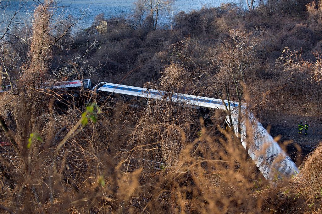 Description of . A derailed Metro-North passenger train lay on its side in the Bronx borough of New York Dec. 1, 2013. The train derailed on a curved section of track in the Bronx on Sunday morning, coming to rest just inches from the water and causing multiple fatalities and dozens of injuries, authorities said. (AP Photo/John Minchillo)
