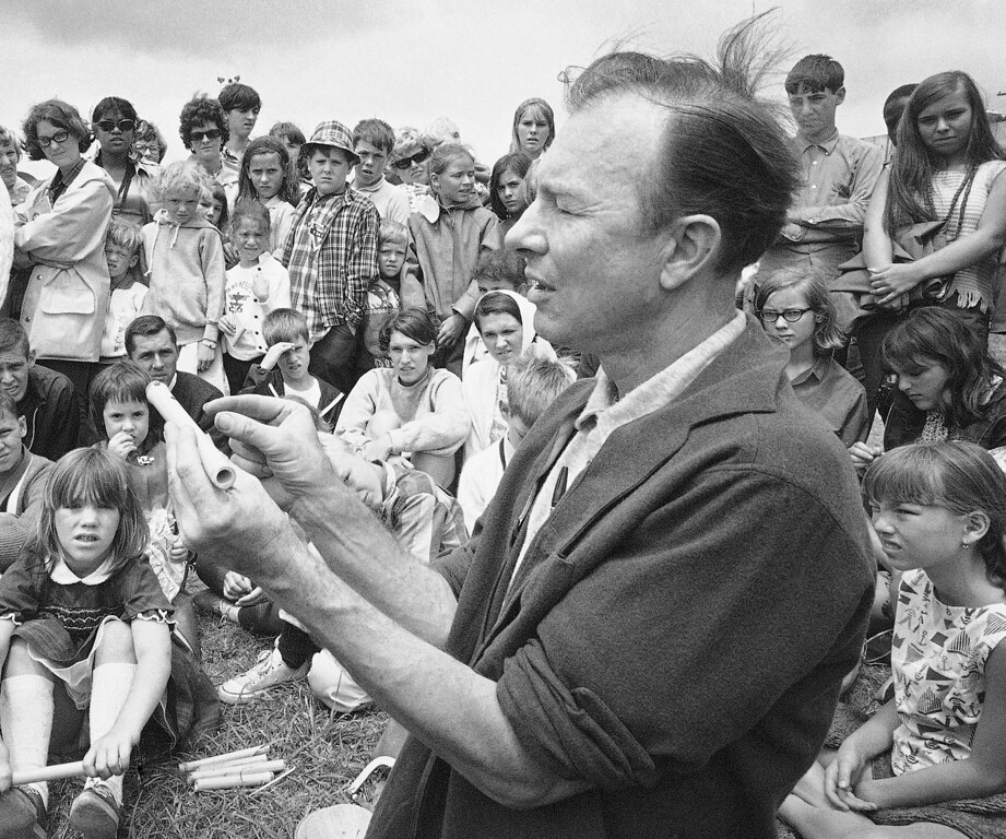 Description of . FILE - In this July 20, 1966, file photo, Pete Seeger conducts an instrument making session on Children's Day at the Newport Folk Festival, in Newport, R.I.  The American troubadour, folk singer and activist Seeger  died Monday Jan. 27, 2014, at age 94. (AP Photo, File)