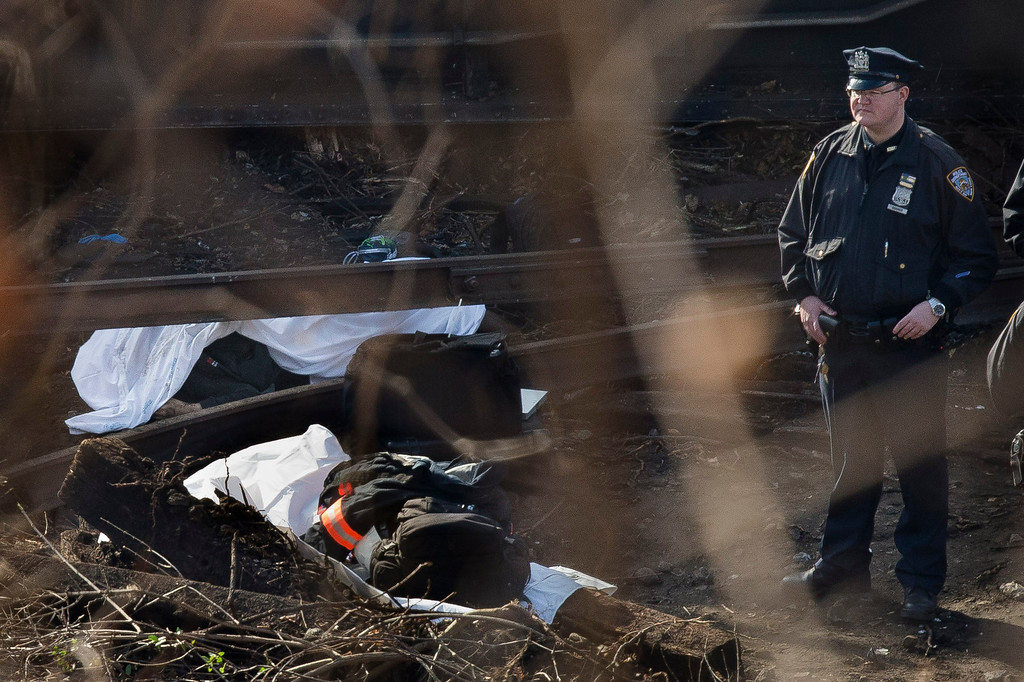 Description of . A police officer stands guard over a body at the scene of a Metro-North passenger train derailment in the Bronx borough of New York, Sunday, Dec. 1, 2013. The train derailed on a curved section of track in the Bronx on Sunday morning, coming to rest just inches from the water and causing multiple fatalities and dozens of injuries, authorities said. (AP Photo/John Minchillo)