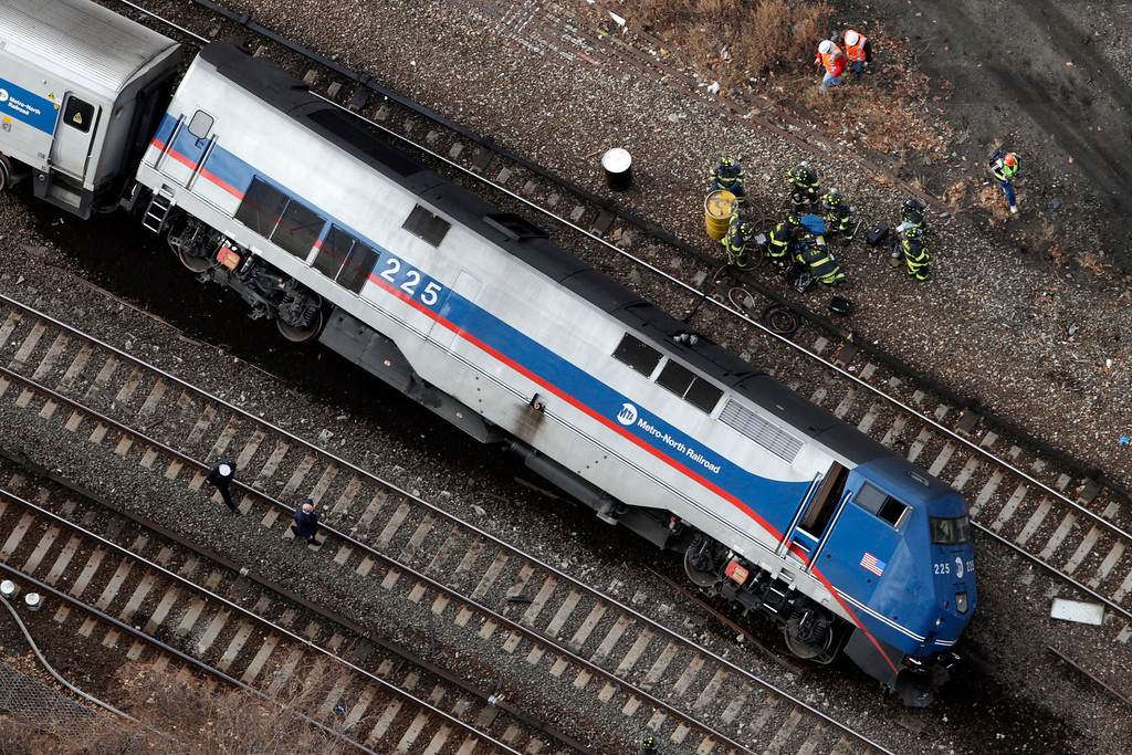 Description of . A Metro-North locomotive lies on its side after derailing, Sunday, Dec. 1, 2013 in the Bronx borough of New York. The train derailed on a curved section of track in the Bronx on Sunday morning, coming to rest just inches from the water and causing multiple fatalities and dozens of injuries, authorities said. (AP Photo/Mark Lennihan)