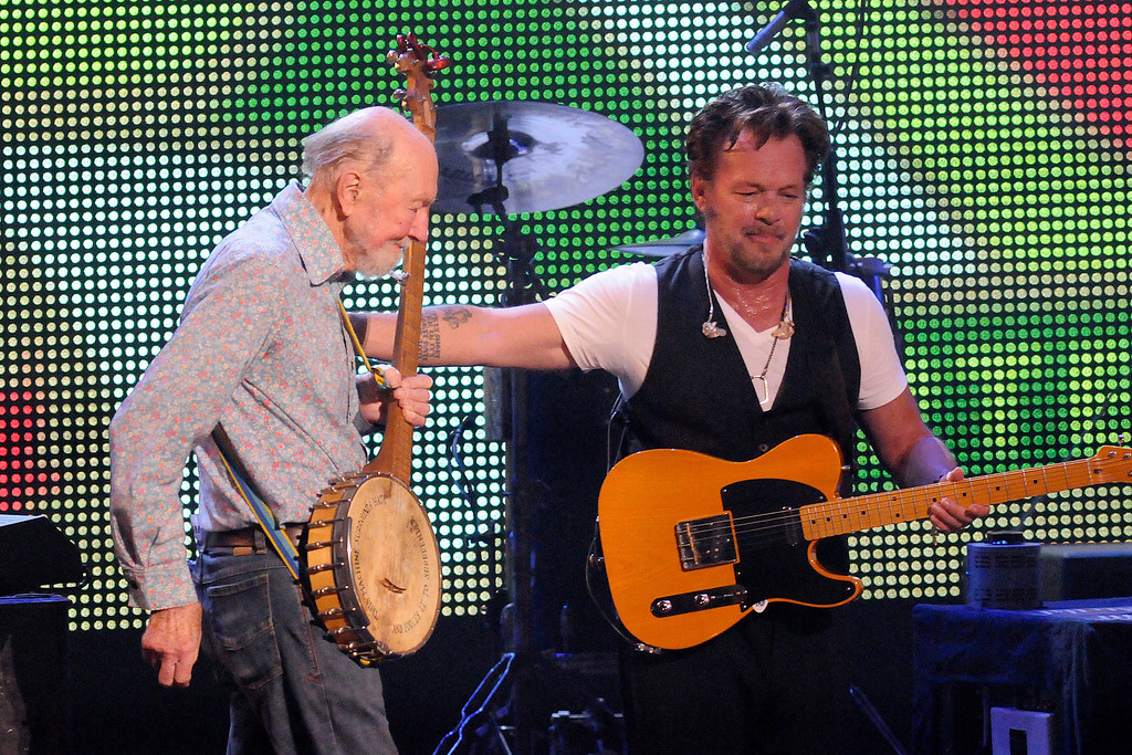 Description of . File-This Sept. 21, 2013, file photo shows Pete Seeger, left, being welcomed on stage by John Mellencamp during the Farm Aid 2013 concert at Saratoga Performing Arts Center in Saratoga Springs, N.Y.  The American troubadour, folk singer and activist Seeger  died Monday Jan. 27, 2014, at age 94.  (AP Photo/Hans Pennink, File)