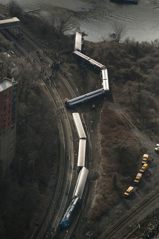 Description of . A Metro-North passenger train lays on it's side after derailing in the Bronx borough of New York, Sunday, Dec. 1, 2013. The train derailed on a curved section of track on Sunday morning, coming to rest just inches from the water and causing multiple fatalities and dozens of injuries, authorities said. Metropolitan Transportation Authority police say the train derailed near the Spuyten Duyvil station. (AP Photo/Mark Lennihan)