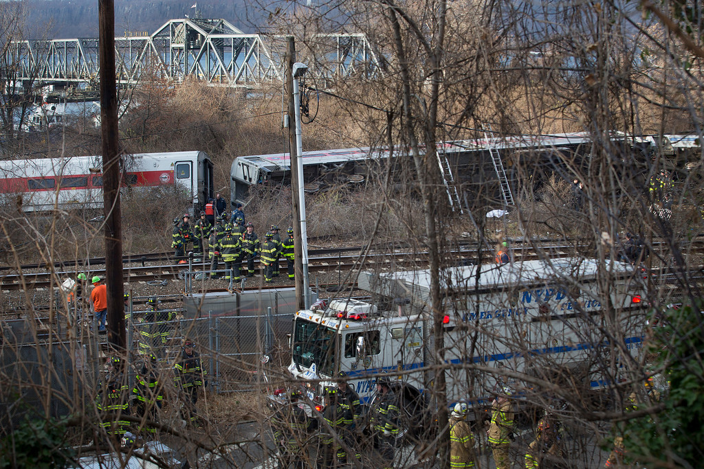 Description of . First responders work the scene of a derailment of a Metro-North passenger train in the Bronx borough of New York Sunday, Dec. 1, 2013. The train derailed on a curved section of track in the Bronx on Sunday morning, coming to rest just inches from the water and causing multiple fatalities and dozens of injuries, authorities said. Metropolitan Transportation Authority police say the train derailed near the Spuyten Duyvil station. (AP Photo/John Minchillo)
