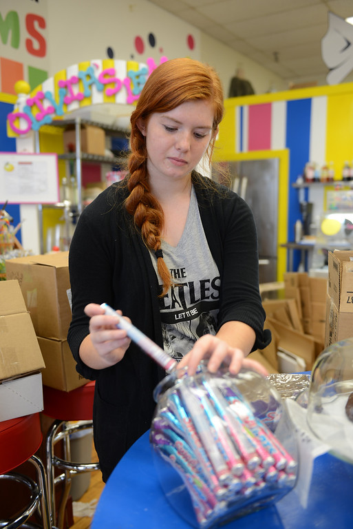 Description of . Tania Barricklo-Daily Freeman Shannon Cowgill, an employee at the newly opened Kingston Candy Bar, stocks some candy after receiving a shipment.