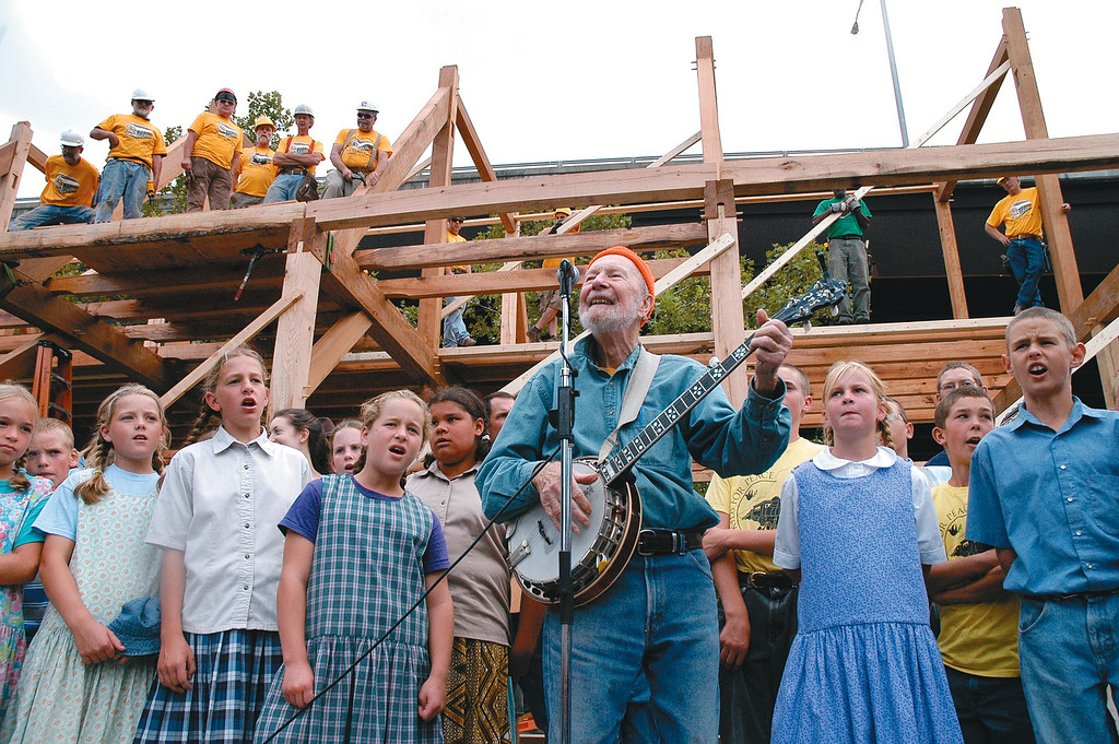 Description of . Set against the backdrop of the barn with the Timber Framers Guild members and Maritime Museum volunteers standing above, Pete Seeger sings his old standard