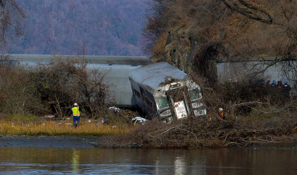 Description of . Viewed from Manhattan, a Metro-North passenger train rests off the tracks after derailing in the Bronx borough of New York, Sunday, Dec. 1, 2013. The train derailed on a curved section of track on Sunday morning, coming to rest just inches from the water and causing multiple fatalities and dozens of injuries, authorities said. Metropolitan Transportation Authority police say the train derailed near the Spuyten Duyvil station. (AP Photo/Craig Ruttle)