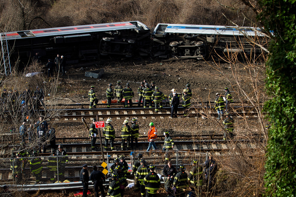 Description of . Emergency personnel respond to the scene of a Metro-North passenger train derailment in the Bronx borough of New York, Sunday, Dec. 1, 2013. The train derailed on a curved section of track in the Bronx on Sunday morning, coming to rest just inches from the water and causing multiple fatalities and dozens of injuries, authorities said. (AP Photo/John Minchillo)