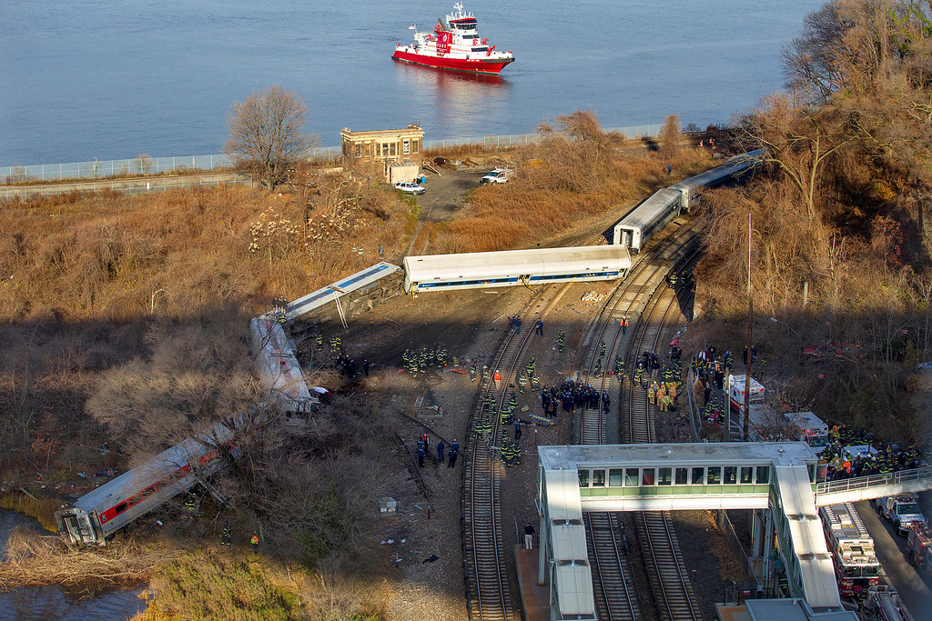 Description of . A New York Fire Department boat approaches the scene of a Metro-North passenger train in the Bronx borough of New York Sunday, Dec. 1, 2013. The train derailed on a curved section of track early Sunday morning, causing