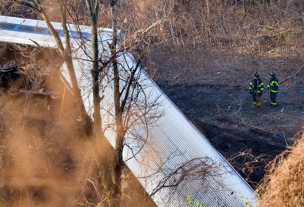 Description of . Emergency rescue personnel work the scene of a Metro-North passenger train derailment in the Bronx borough of New York, Sunday, Dec. 1, 2013. The train derailed on a curved section of track on Sunday morning, coming to rest just inches from the water and causing multiple fatalities and dozens of injuries, authorities said. Metropolitan Transportation Authority police say the train derailed near the Spuyten Duyvil station. (AP Photo/Craig Ruttle)