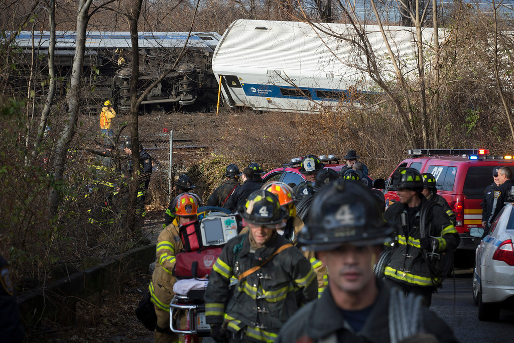 Description of . Firefighters respond to the scene of a Metro-North passenger train derailment in the Bronx borough of New York Sunday, Dec. 1, 2013. The train derailed on a curved section of track in the Bronx on Sunday morning, coming to rest just inches from the water and causing multiple fatalities and dozens of injuries, authorities said. Metropolitan Transportation Authority police say the train derailed near the Spuyten Duyvil station. (AP Photo/John Minchillo)