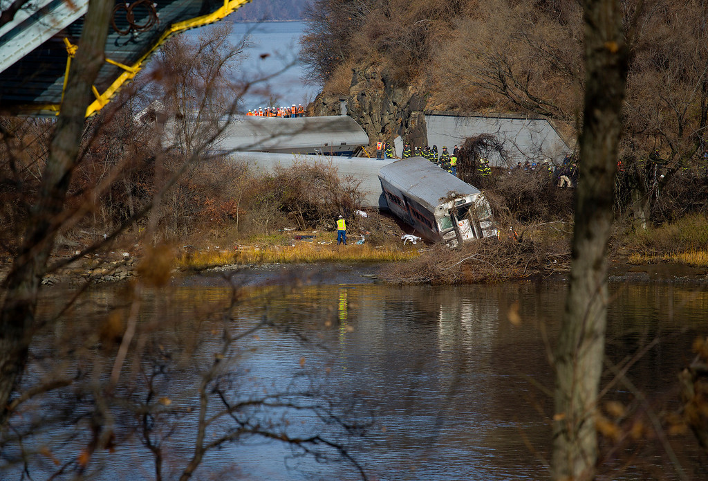 Description of . Viewed from Manhattan, Emergency rescue personnel work the scene of a Metro-North passenger train derailment in the Bronx borough of New York, Sunday, Dec. 1, 2013. The train derailed on a curved section of track on Sunday morning, coming to rest just inches from the water and causing multiple fatalities and dozens of injuries, authorities said. Metropolitan Transportation Authority police say the train derailed near the Spuyten Duyvil station. (AP Photo/Craig Ruttle)