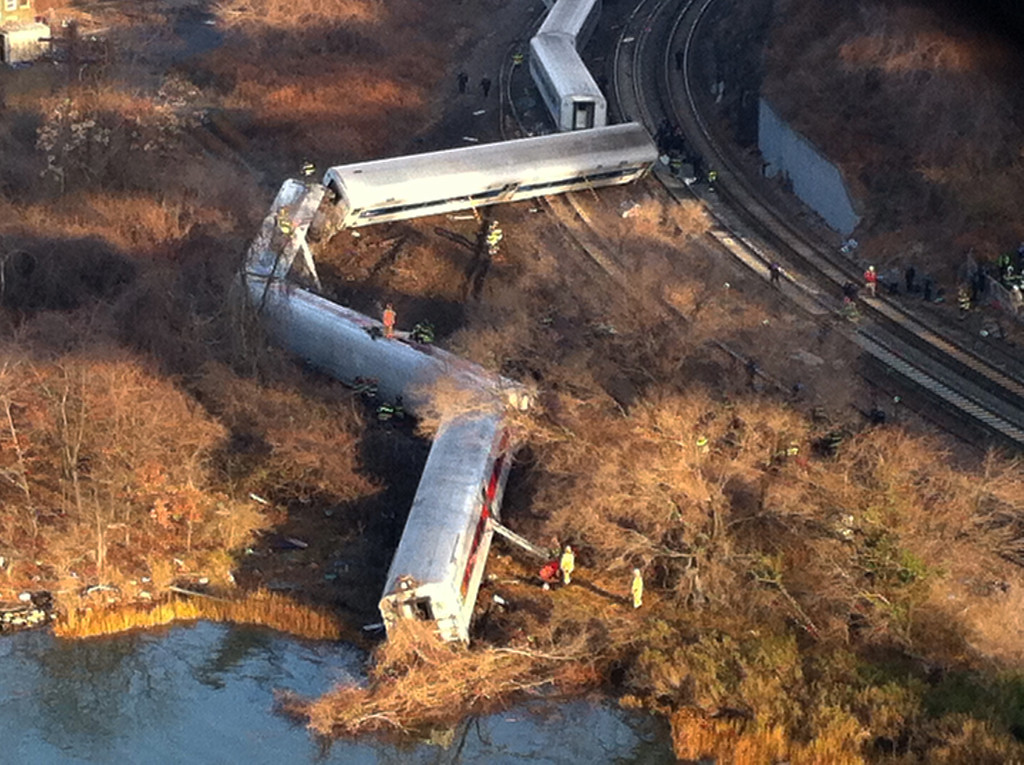 Description of . Cars from a Metro-North passenger train are scattered after the train derailed in the Bronx neighborhood of New York, Sunday, Dec. 1, 2013. The Fire Department of New York says there are