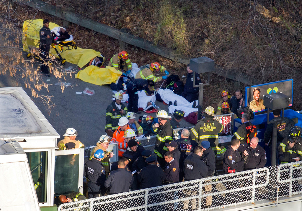 Description of . Injured people are tended to by first responders near the site of the derailment of a Metro-North passenger train in the Bronx borough of New York, Sunday, Dec. 1, 2013. The train derailed on a curved section of track in the Bronx on Sunday morning, coming to rest just inches from the water and causing multiple fatalities and dozens of injuries, authorities said. Metropolitan Transportation Authority police say the train derailed near the Spuyten Duyvil station. (AP Photo/Craig Ruttle)