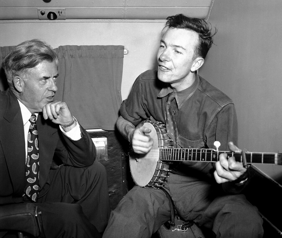Description of . File-This Aug. 28, 1948, file photo shows Henry A. Wallace, listening to Pete Seeger, his banjo-playing singer, on a plane between Norfolk and Richmond, Va.  The American troubadour, folk singer and activist Seeger  died Monday Jan. 27, 2014, at age 94. (AP Photo/File)