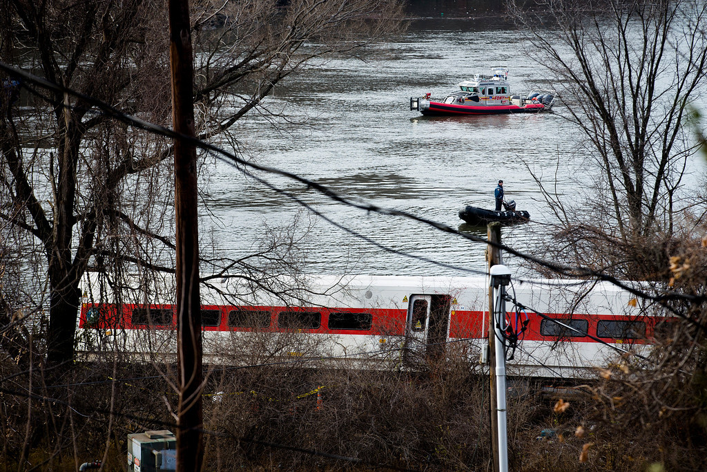 Description of . A New York Fire Department boat responds to the scene of a Metro-North passenger train derailment in the Bronx borough of New York Sunday, Dec. 1, 2013. The train derailed on a curved section of track in the Bronx on Sunday morning, coming to rest just inches from the water and causing multiple fatalities and dozens of injuries, authorities said. (AP Photo/John Minchillo)