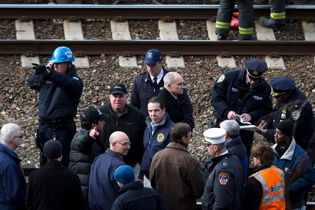 Description of . New York Governor Andrew Coumo, center, NYPD Police Commissioner Ray Kelly, center right, and MTA Chairman and CEO Thomas Prendergast, center left, stand by the tracks at the scene of a Metro-North passenger train derailment in the Bronx borough of New York, Sunday, Dec. 1, 2013. The train derailed on a curved section of track in the Bronx on Sunday morning, coming to rest just inches from the water and causing multiple fatalities and dozens of injuries, authorities said. (AP Photo/John Minchillo)