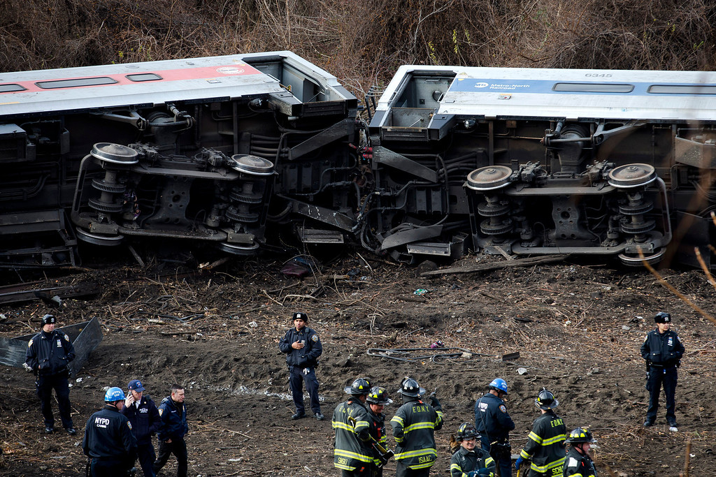 Description of . Emergency personnel respond to the scene of a Metro-North passenger train derailment in the Bronx borough of New York Sunday, Dec. 1, 2013. The train derailed on a curved section of track in the Bronx on Sunday morning, coming to rest just inches from the water and causing multiple fatalities and dozens of injuries, authorities said. Metropolitan Transportation Authority police say the train derailed near the Spuyten Duyvil station. (AP Photo/John Minchillo)