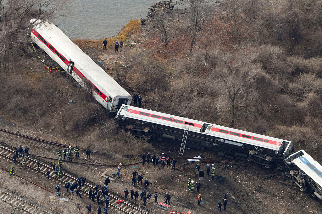 Description of . Emergency rescue personnel work the scene of a Metro-North passenger train derailment in the Bronx borough of New York, Sunday, Dec. 1, 2013. The train derailed on a curved section of track on Sunday morning, coming to rest just inches from the water and causing multiple fatalities and dozens of injuries, authorities said. Metropolitan Transportation Authority police say the train derailed near the Spuyten Duyvil station. (AP Photo/Mark Lennihan)