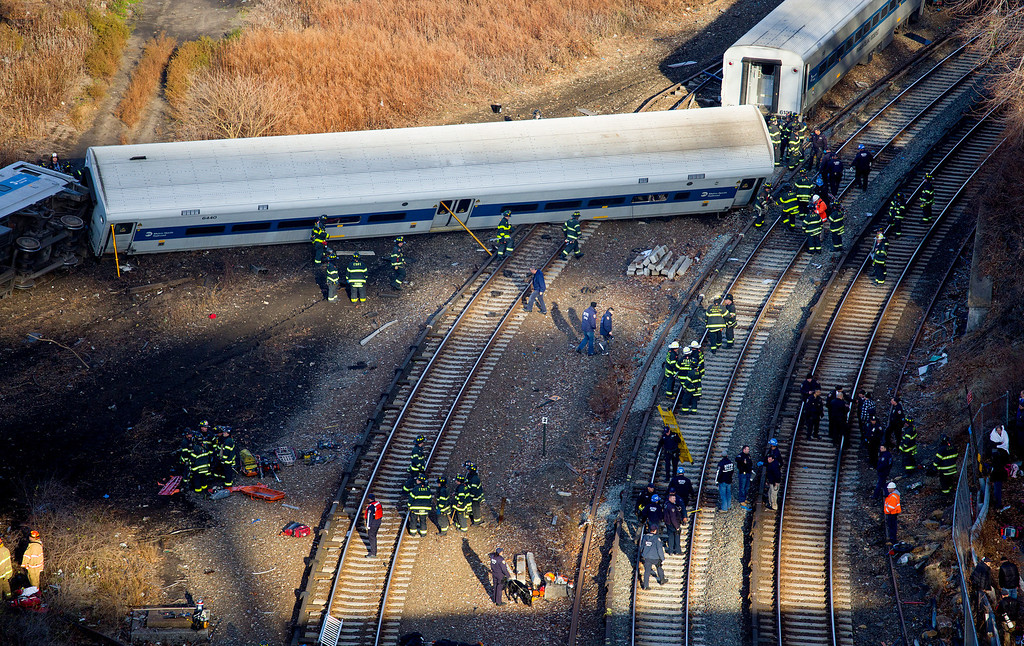 Description of . First responders gather at the derailment of a Metro-North passenger train in the Bronx borough of New York Sunday, Dec. 1, 2013. The train derailed on a curved section of track in the Bronx on Sunday morning, coming to rest just inches from the water and causing multiple fatalities and dozens of injuries, authorities said. Metropolitan Transportation Authority police say the train derailed near the Spuyten Duyvil station. (AP Photo/Craig Ruttle)