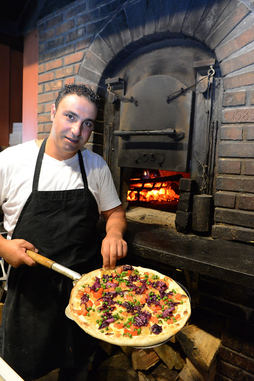 . Tania Barricklo-Daily Freeman Ammar Chamas. co-owner of La Florentina at 606 Ulster Ave. holds out the Amatriciana pizza, an unusual but popular pizza made with peas, red cabbage, onions with a  porcini mushroom sauce, baked in a wood-fired oven.