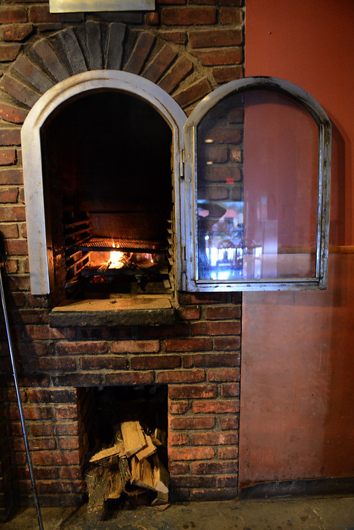 . Tania Barricklo-Daily Freeman A wood-fired grill which is used for fish and steaks amongst other things is next to the oven used for baking.