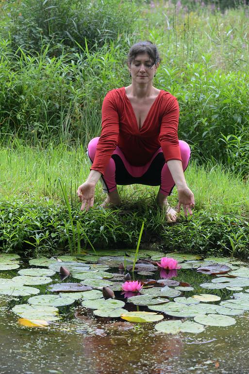 . Tania Barricklo-Daily Freeman Linda Lalita Winnick strikes a meditation pose in front of a lily pond at Shakti Yoga at 1685 Sawkilll Rd.
