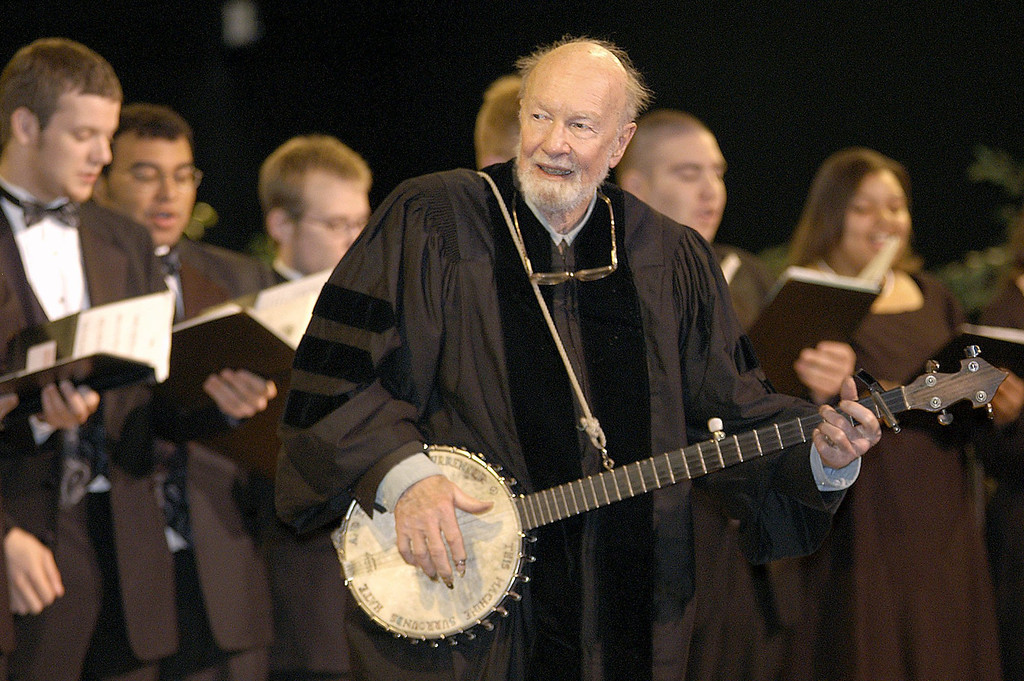 """. File-This May 10, 2003 file photo shows folk singer Pete Seeger performing\""""When the Saints Go Marching In\"""" with the Saint Rose Chamber Singers during commencement ceremonies for the College of St. Rose at the Empire State Plaza in Albany, N.Y.   The American troubadour, folk singer and activist Seeger  died Monday Jan. 27, 2014, at age 94.  (AP Photo/Stewart Cairns, File)"""