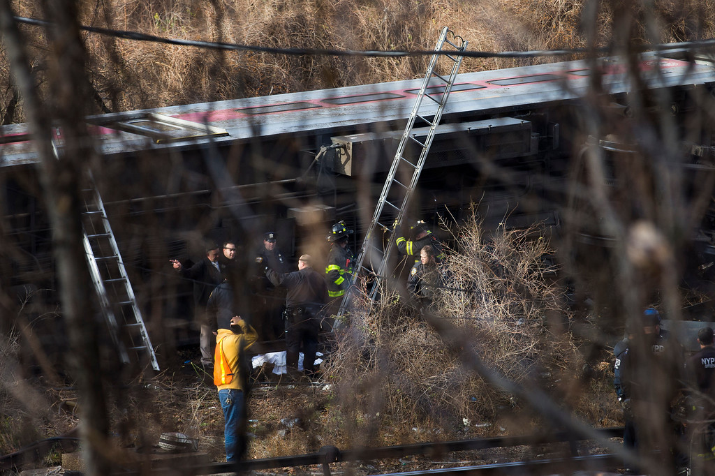 . Emergency personnel respond to the scene of a Metro-North passenger train derailment in the Bronx borough of New York, Sunday, Dec. 1, 2013. The train derailed on a curved section of track in the Bronx on Sunday morning, coming to rest just inches from the water and causing multiple fatalities and dozens of injuries, authorities said. (AP Photo/John Minchillo)