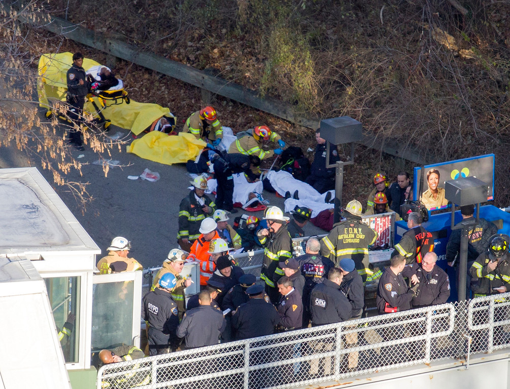 . Injured people are tended to by first responders near the site of the derailment of a Metro-North passenger train in the Bronx borough of New York, Sunday, Dec. 1, 2013. The train derailed on a curved section of track in the Bronx on Sunday morning, coming to rest just inches from the water and causing multiple fatalities and dozens of injuries, authorities said. Metropolitan Transportation Authority police say the train derailed near the Spuyten Duyvil station. (AP Photo/Craig Ruttle)