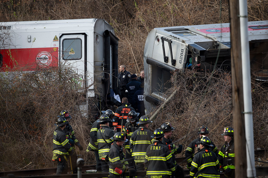 . CORRECTS BYLINE TO JOHN MINCHILLO - Emergency personnel gather at the scene of the derailment of a Metro-North passenger train in the Bronx borough of New York Sunday, Dec. 1, 2013.  The train derailed on a curved section of track in the Bronx on Sunday morning, coming to rest just inches from the water and causing multiple fatalities and dozens of injuries, authorities said. Metropolitan Transportation Authority police say the train derailed near the Spuyten Duyvil station. (AP Photo/John Minchillo)