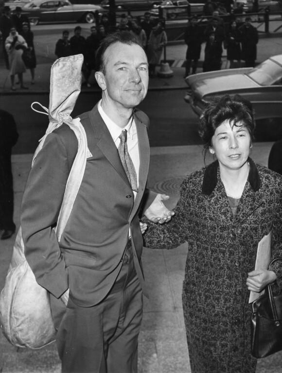 . File-This April 4, 1961, file photo shows American folk singer Pete Seeger, a banjo slung over his shoulder, being accompanied by his wife Toshi, on his arrival at the Federal Court, in New York.   The American troubadour, folk singer and activist Seeger  died Monday Jan. 27, 2014, at age 94. (AP Photo/File)