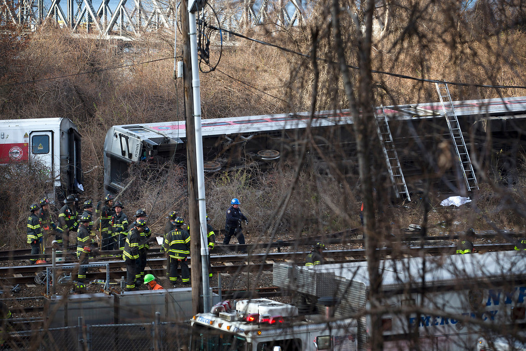 . Emergency personnel work the scene of the derailment of a Metro-North passenger train in the Bronx borough of New York Sunday, Dec. 1, 2013. The train derailed on a curved section of track in the Bronx on Sunday morning, coming to rest just inches from the water and causing multiple fatalities and dozens of injuries, authorities said. Metropolitan Transportation Authority police say the train derailed near the Spuyten Duyvil station. (AP Photo/John Minchillo)