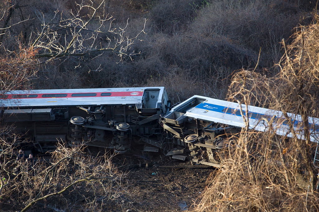 ". Passenger cars are on their side after a Metro-North train derailed in the Bronx on Sunday morning, Dec. 1, 2013 causing ""multiple injuries,\"" authorities said. Metropolitan Transportation Authority police say the train derailed near the Spuyten Duyvil station. (AP Photo/Craig Ruttle)"