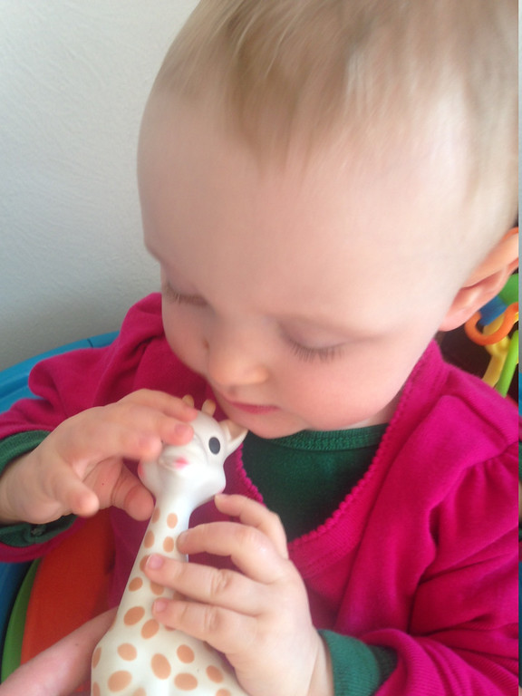 """. \""""Progress-holding a toy and bringing it to her mouth\"""""""