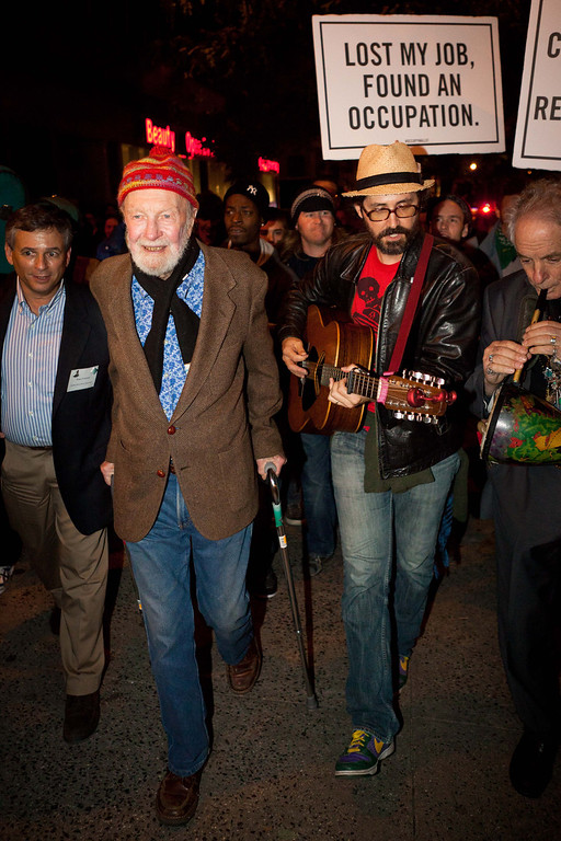 . File-This Oct. 21, 2011 file photo shows activist musician Pete Seeger, 92, left, marching with nearly a thousand demonstrators sympathetic to the Occupy Wall Street protests for a brief acoustic concert in Columbus Circle in New York.   The American troubadour, folk singer and activist Seeger  died Monday Jan. 27, 2014, at age 94.  (AP Photo/John Minchillo, File)